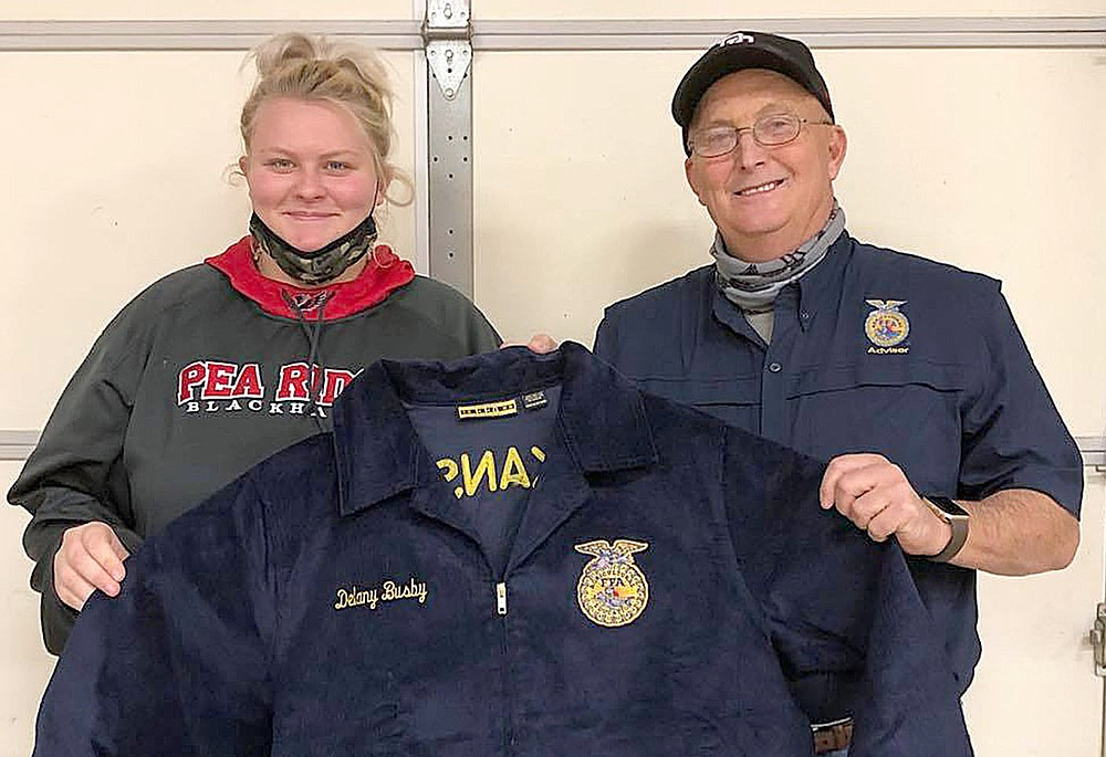 PRHS student Delaney Busby received her FFA jacket from teacher Perry Mason.