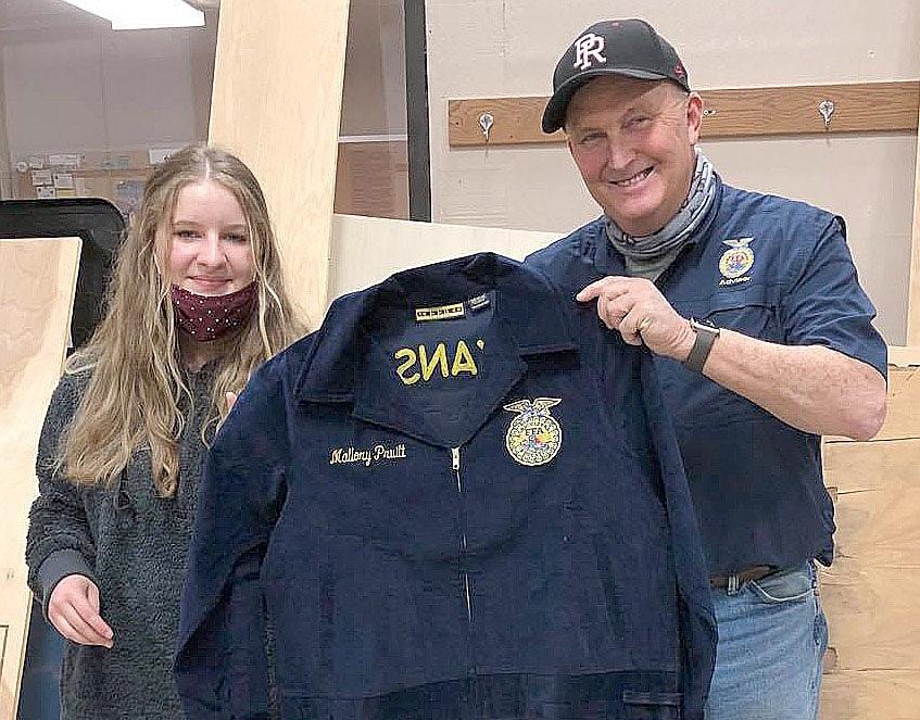 PRHS FFA student Mallory Pruitt receives her jacket from teacher Perry Mason.