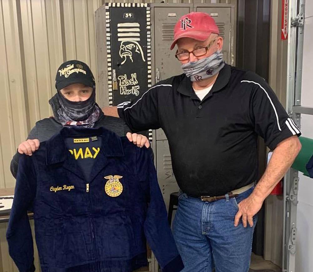 Cayden Regan received his FFA jacket from teacher Perry Mason.