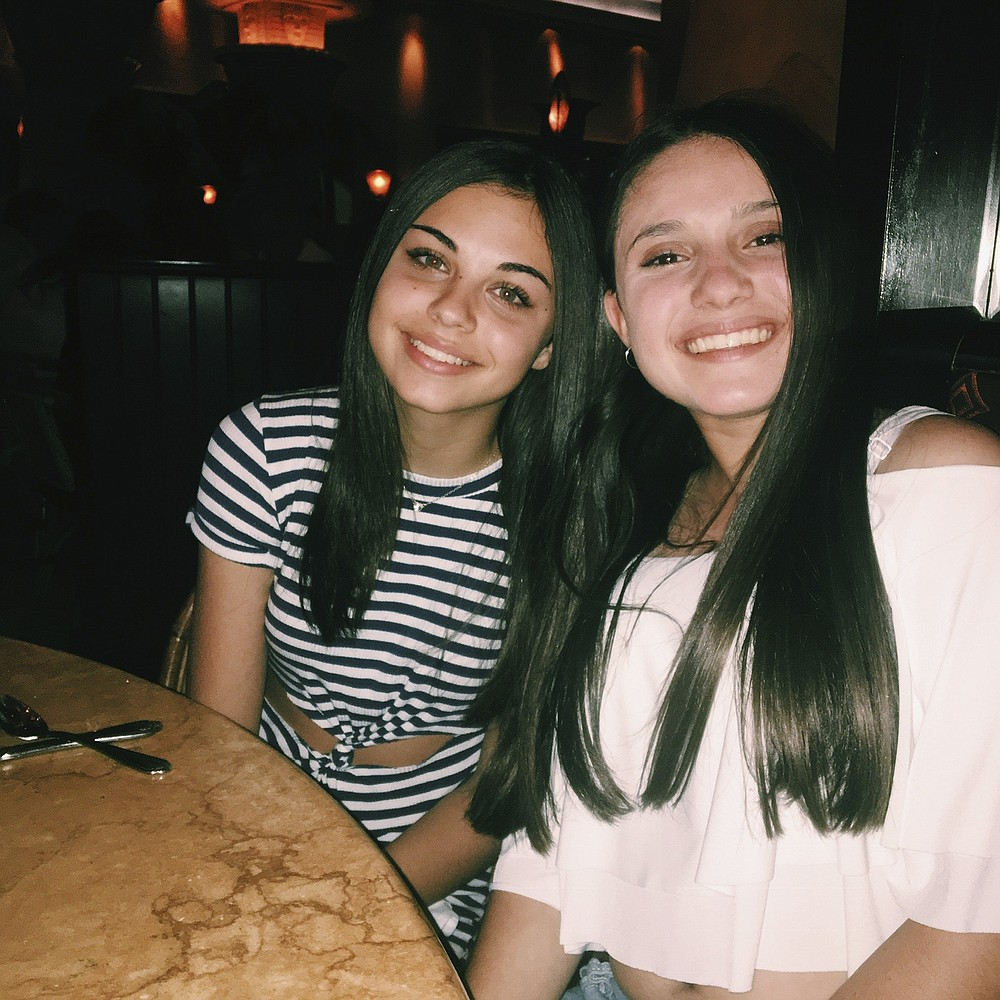 In this undated photo made available by Lori Alhadeff, her daughter Alyssa, right, sits at a table with her best friend Abby Price. Alyssa was killed in the 2018 Valentine's Day massacre at Marjory Stoneman Douglas High School in Parkland, Fla. Abby's family moved to North Carolina for her junior year hoping for a fresh start. She was terrified of a new school, forging new friendships and then COVID hit, marring the rest of her high school experience. (Lori Alhadeff via AP)