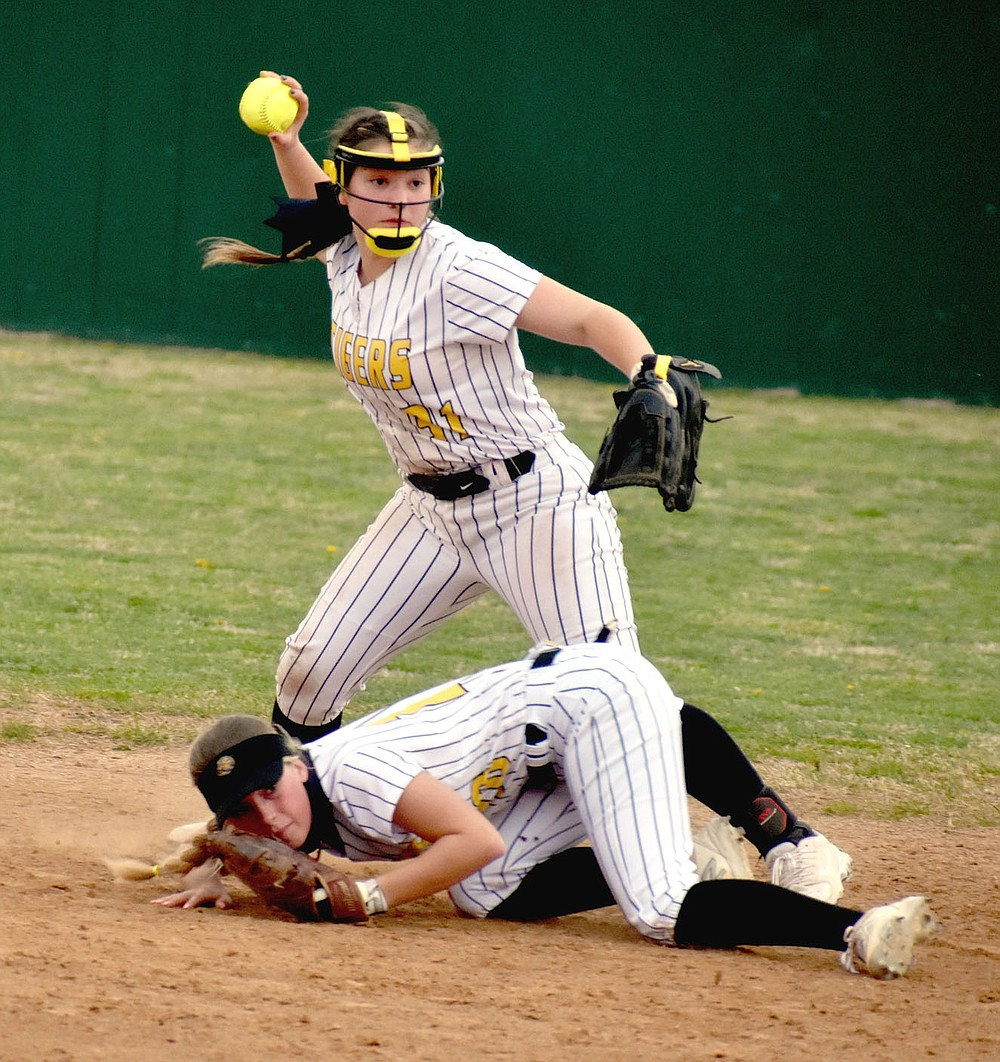 MARK HUMPHREY  ENTERPRISE-LEADER/Picture perfect teamwork. Prairie Grove senior shortstop Makinsey Parnell comes to the aid of classmate Sydney Stearman, who dove on the ground to stop a hit in the infield, but couldn't get up in time to make the throw to first. Parnell took care of that chore, recording the third out to give the Lady Tigers a chance trailing 5-2 coming into their last at-bat and win 6-5 with four runs crossing the plate in the bottom of the seventh against Berryville.