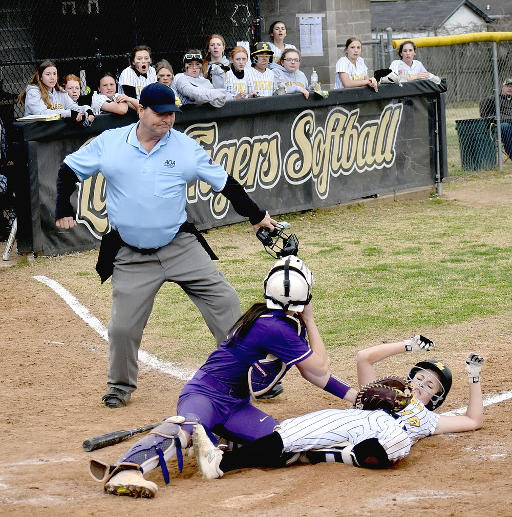 MARK HUMPHREY  ENTERPRISE-LEADER/The Berryville catcher applies a tag to Prairie Grove senior Sydney Stearman waved in from second by Lady Tiger coach Dave Torres with one out. The brilliant throw home by Lady Bobcats outfielder LoraGrace Hill had a downside for Berryville because it allowed Makinsey Parnell to turn a single into a double. She scored on Kelsey Pickett's double to end the game with Prairie Grove winning 6-5 after beginning the seventh inning with a 3-run deficit on Tuesday, March 30.