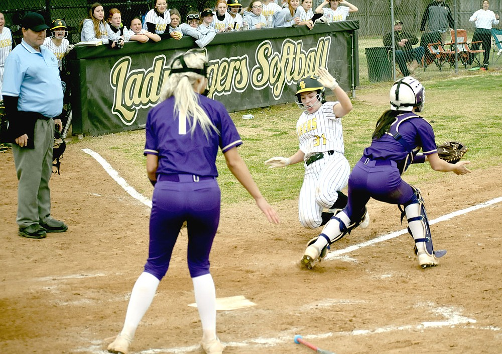 MARK HUMPHREY  ENTERPRISE-LEADER/Prairie Grove senior Makinsey Parnell goes into a slide while squeezing past Berryville catcher with Lady Bobcat pitcher Faith Kelley backing up at the plate. Parnell scored the winning run on this play after delivering a base hit to keep the Lady Tigers alive in the bottom of the seventh. Kelsey Pickett doubled to bring Parnell home as Prairie Grove emerged with a 6-5 win to start 4A-1 Conference softball play.