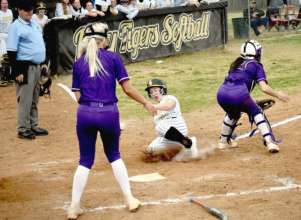 MARK HUMPHREY  ENTERPRISE-LEADER/Prairie Grove senior Makinsey Parnell slides into home between Berryville's catcher and pitcher Faith Kelley backing up at the plate. Parnell took off from second when teammate Kelsey Pickett doubled. The throw to the plate veered off towards Prairie Grove's dugout. Parnell's run won the 4A-1 Conference softball opener for Prairie Grove, 6-5, on Tuesday, March 30.