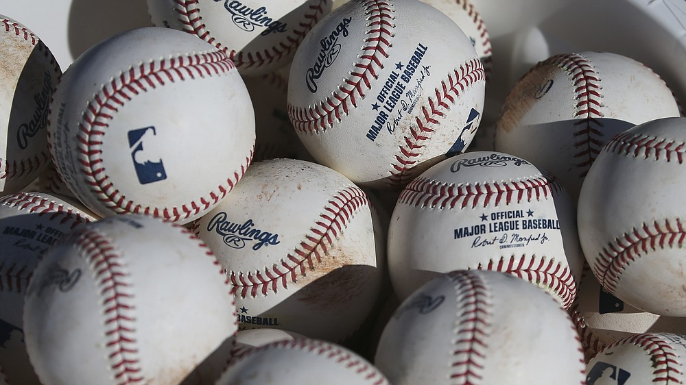 FILE - In this Feb. 14, 2020, file photo, baseballs sit in a bucket after they were used for fielding practice during spring training baseball workouts for pitchers and catchers at Cleveland Indians camp in Avondale, Ariz. Major League Baseball revamped its spring training exhibition schedule because of the pandemic, cutting travel for Florida-based teams in an effort to avoid the novel coronavirus, the league announced Friday, Feb. 12, 2021. (AP Photo/Ross D. Franklin, File)