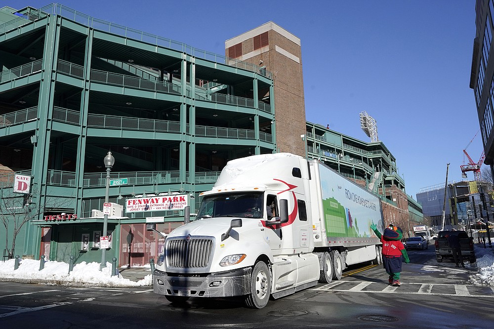 Wally the Green Monster, the team's mascot, right, waves as a Boston Red Sox baseball equipment truck departs Fenway Park, Monday, Feb. 8, 2021, in Boston on its way to the team's spring training facility, in Fort Myers, Fla.  (AP Photo/Steven Senne)
