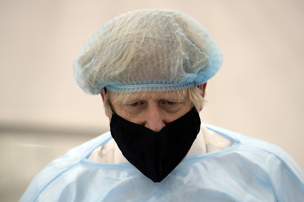 Britain's Prime Minister Boris Johnson, wearing a face mask to prevent the spread of the coronavirus, visits a PPE manufacturing facility during a visit to the north east of England, in Seaton Delaval, England, Saturday, Feb. 13, 2021. (AP Photo/Scott Heppell, Pool)