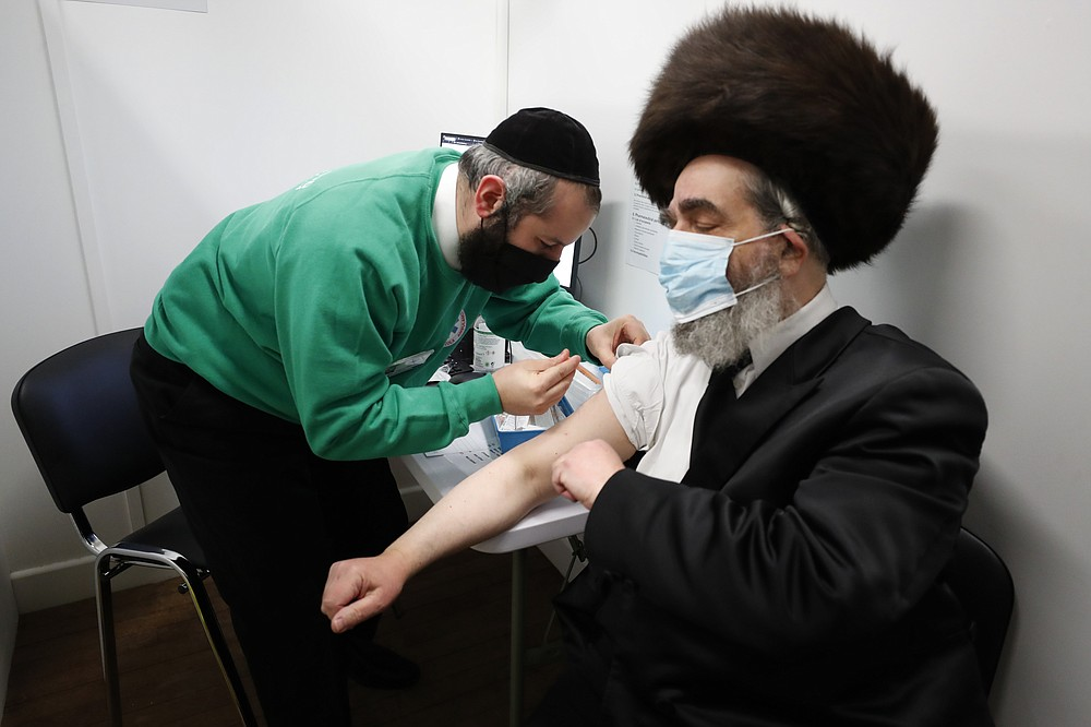 Rabbi Bieberfeld receives a dose coronavirus vaccine at the John Scott Vaccination Centre in London, Saturday, Feb. 13, 2021. The dose was administered at an event to encourage vaccine uptake in Britain's Haredi community which has been hard hit during the COVID-19 pandemic. (AP Photo/Frank Augstein)