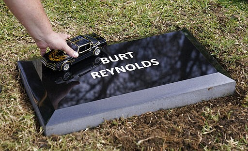 """Burt Reynolds fan Dan Redmond, of Calamesa, Calif., places a model of the Trans Am from the 1977 film """"Smokey and the Bandit"""" on a temporary headstone for the late actor at Hollywood Forever cemetery, Thursday, Feb. 11, 2021, in Los Angeles. Reynolds' cremated remains were moved from Florida to Hollywood Forever, where a small ceremony was held Thursday. A permanent gravesite will be put up for Reynolds in a few months. (AP Photo/Chris Pizzello)"""