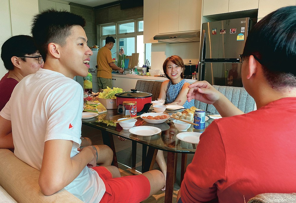 Chan Jit Yen smiles as she hosts Malaysian students, foreground, during a Lunar New Year hot pot lunch at her rented apartment in Singapore Saturday, Feb. 13, 2021. With Malaysian workers and students stranded in the city state over the Lunar New Year due to coronavirus travel restrictions, the Malaysian Association in Singapore has called on Malaysians to treat students to a meal. (AP Photo/Annabelle Liang)
