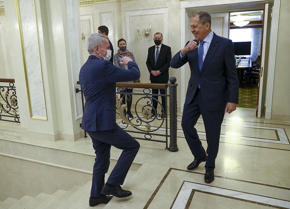 In this handout photo released by Russian Foreign Ministry Press Service, Finnish Foreign Minister Pekka Haavisto, left, and Russian Foreign Minister Sergey Lavrov, both wearing face masks to protect against coronavirus greet each other prior to their talks in St. Petersburg, Russia, Monday, Feb. 15, 2021. Lavrov blamed the European Union for a freeze in ties and argued that Moscow remains ready to mend relations. (Russian Foreign Ministry Press Service via AP)