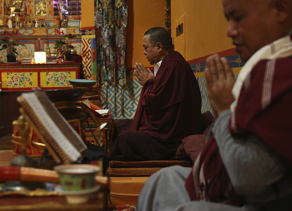 Lama Gelbu, left, and Pasang Sherpa, right, partake in the traditional Buddhist Dakini Day practice, a group meditation that includes song and food and is celebrated on the 25th day of each lunar month, at the United Sherpa Association in the Queens borough of New York on Friday, Jan. 8, 2021. (AP Photo/Jessie Wardarski)