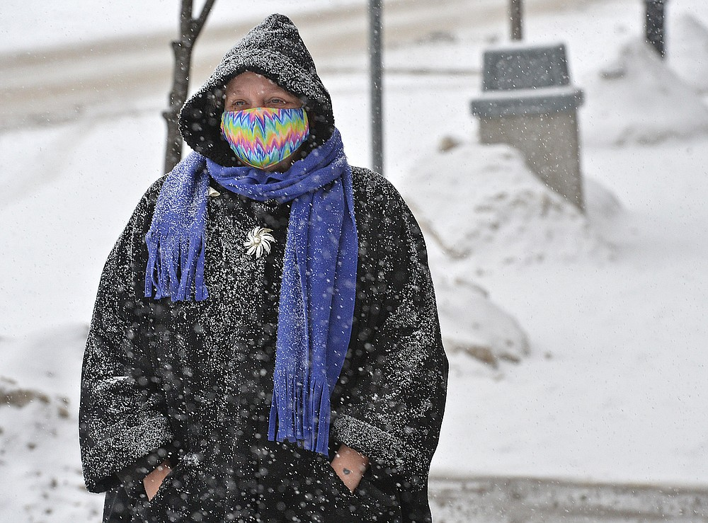 Diane Phelps, 54, walks along Main Street in Girard, Pa., during a morning snowfall on Monday, Feb. 15, 2021. A storm expected in northwest Pennsylvania and western New York region is predicted to drop up several inches of snow by Tuesday afternoon. (Christopher Millette/Erie Times-News via AP)