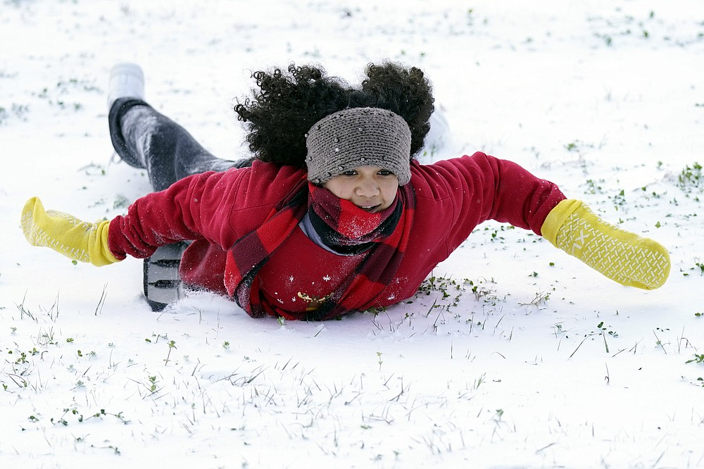 Alyssa Remi, 12, slides down a snow covered hill Monday, Feb. 15, 2021, in Houston.A winter storm dropping snow and ice sent temperatures plunging across the southern Plains, prompting a power emergency in Texas a day after conditions canceled flights and impacted traffic across large swaths of the U.S. (AP Photo/David J. Phillip)
