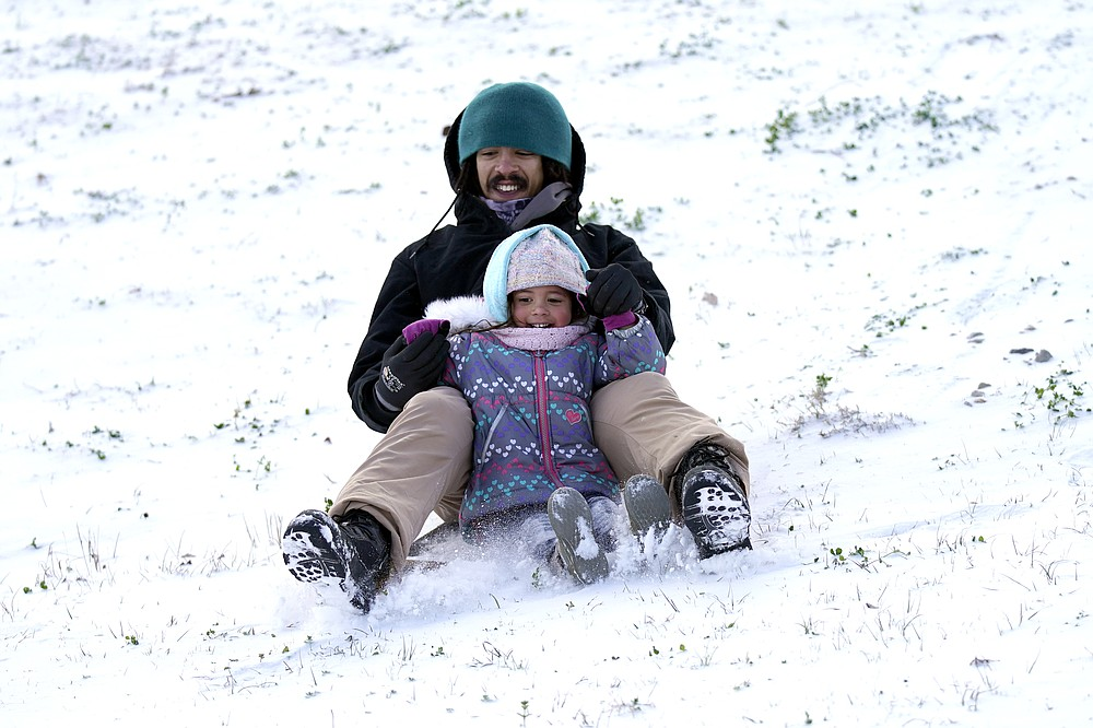 Robert Savannah and his daughter Sophia, 4, slide down a snow covered hill Monday, Feb. 15, 2021, in Houston. A winter storm dropping snow and ice sent temperatures plunging across the southern Plains, prompting a power emergency in Texas a day after conditions canceled flights and impacted traffic across large swaths of the U.S. (AP Photo/David J. Phillip)