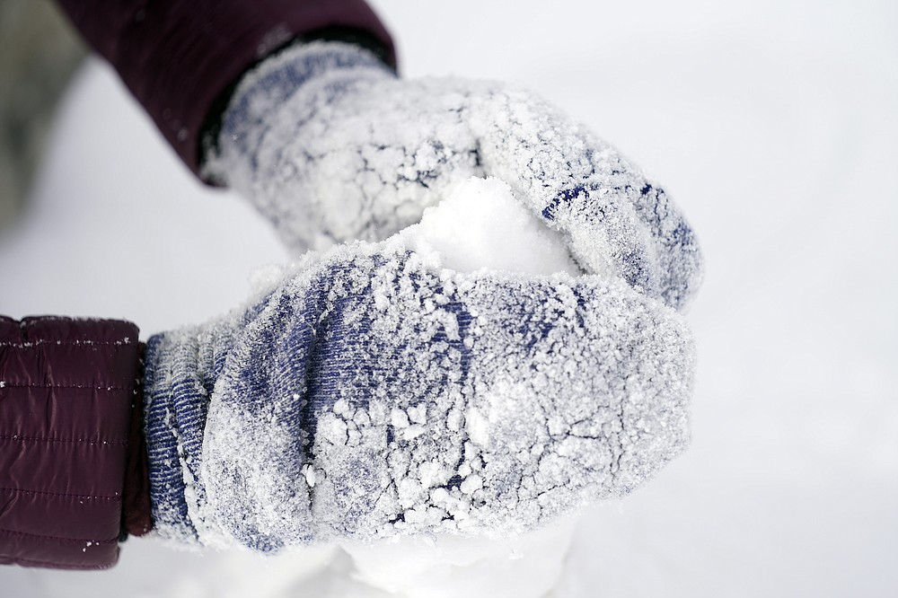Cristina Lucero's hands are covered in snow while building a snowman Monday, Feb. 15, 2021, in Houston. A winter storm dropping snow and ice sent temperatures plunging across the southern Plains, prompting a power emergency in Texas a day after conditions canceled flights and impacted traffic across large swaths of the U.S. (AP Photo/David J. Phillip)