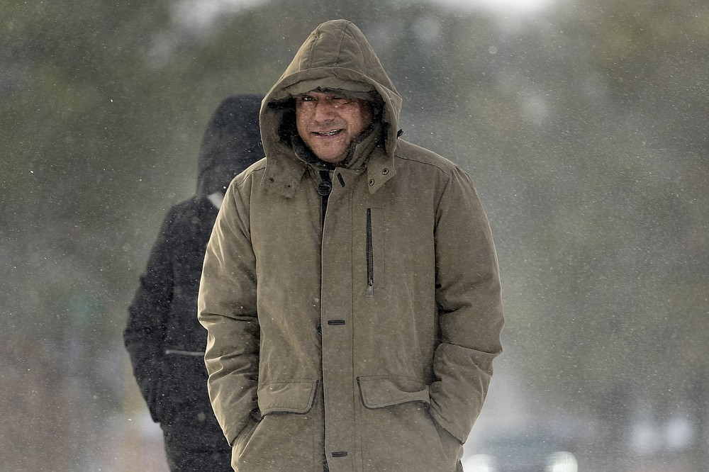 Erasmo Vazquez walks through blowing snow Monday, Feb. 15, 2021, in Houston. A winter storm dropping snow and ice sent temperatures plunging across the southern Plains, prompting a power emergency in Texas a day after conditions canceled flights and impacted traffic across large swaths of the U.S. (AP Photo/David J. Phillip)