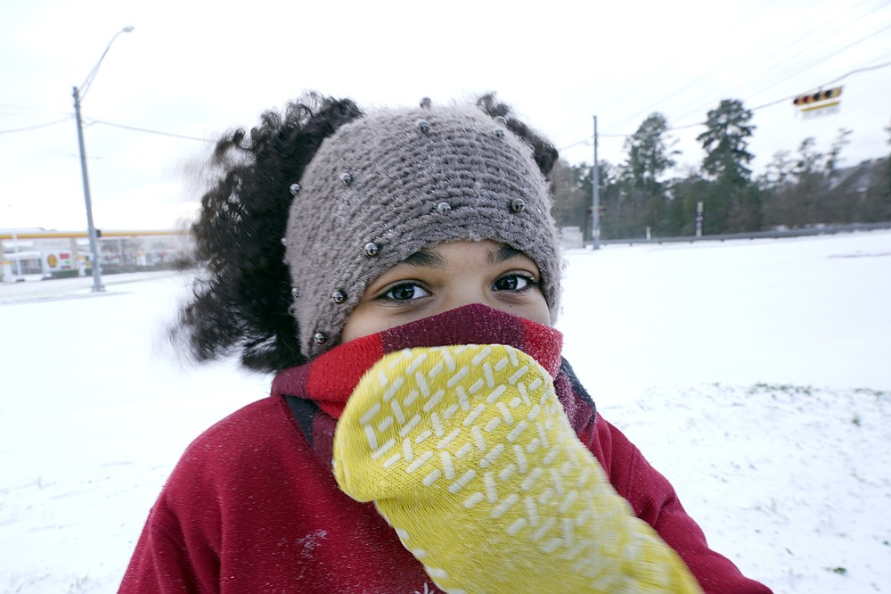Alyssa Remi, 12, tries to keep warm while playing in the snow Monday, Feb. 15, 2021, in Houston. A winter storm dropping snow and ice sent temperatures plunging across the southern Plains, prompting a power emergency in Texas a day after conditions canceled flights and impacted traffic across large swaths of the U.S. (AP Photo/David J. Phillip)