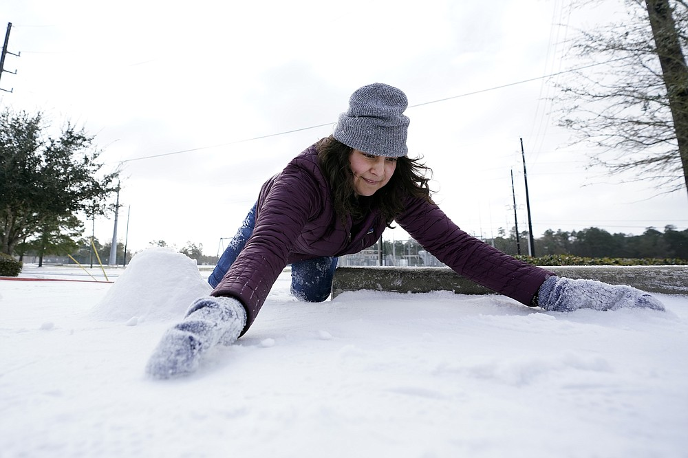 Cristina Lucero gathers snow while trying to build a snowman Monday, Feb. 15, 2021, in Houston. A winter storm dropping snow and ice sent temperatures plunging across the southern Plains, prompting a power emergency in Texas a day after conditions canceled flights and impacted traffic across large swaths of the U.S. (AP Photo/David J. Phillip)