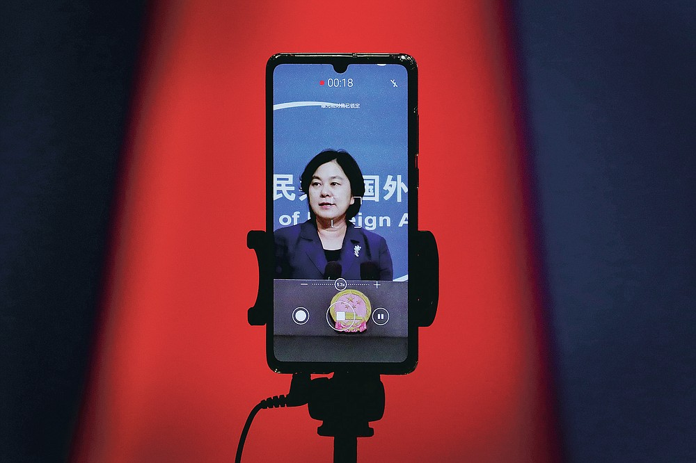"""FILE - In this Sept. 1, 2020 file photo, a smartphone records Chinese Foreign Ministry spokeswoman Hua Chunying as she speaks during a daily briefing at the Ministry of Foreign Affairs in Beijing. """"I'd like to stress that if the United States truly respects facts, it should open the biological lab at Fort Detrick, give more transparency to issues like its 200-plus overseas bio-labs, invite WHO experts to conduct origin-tracing in the United States,"""" she said at a January 2021 MOFA press conference that went viral in China. (AP Photo/Andy Wong)"""