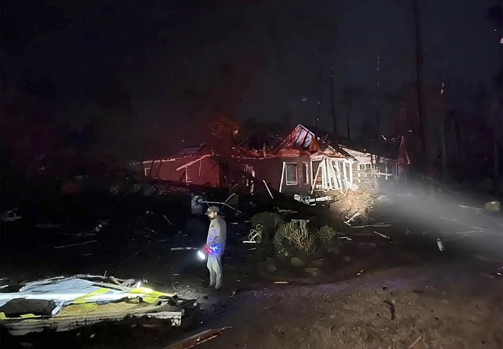 Un homme examine les dégâts après qu'une tornade meurtrière a ravagé le comté de Brunswick, en Caroline du Nord, le mardi 16 février 2021. Les autorités de la Caroline du Nord disent que plusieurs personnes sont mortes et que d'autres ont été blessées après qu'une tornade a ravagé le comté de Brunswick, laissant une trace de lourdes destructions. .  (Emily Flax / Bureau du shérif du comté de Brunswick via AP)