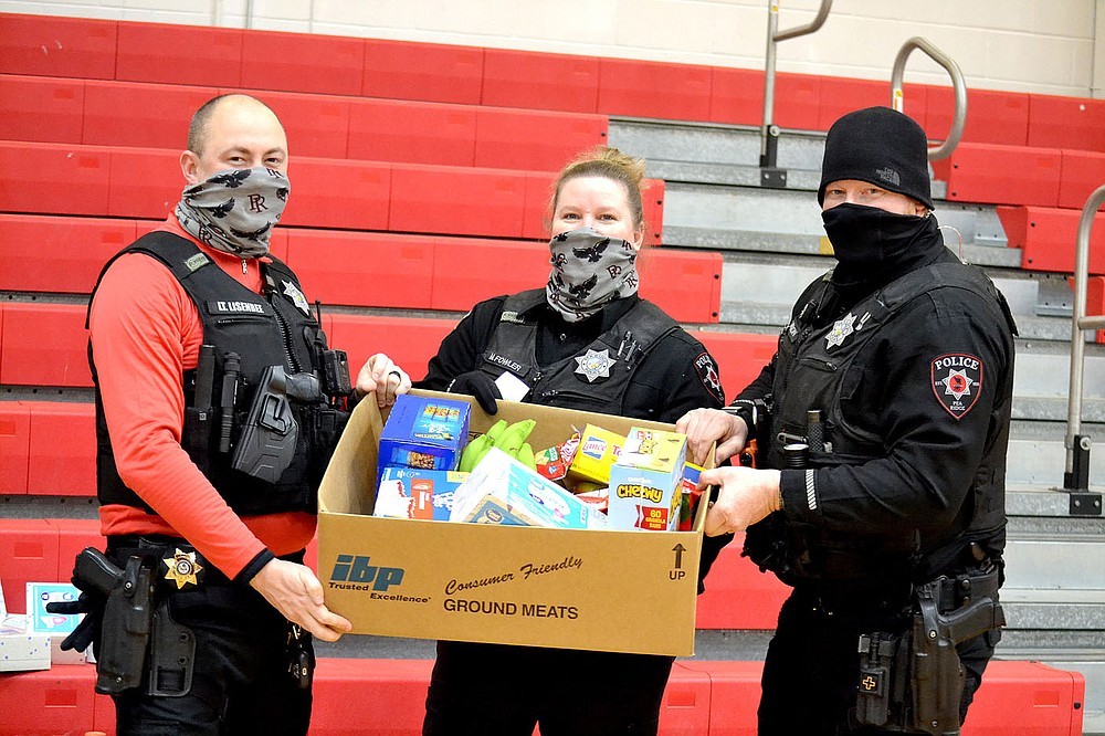 Pea Ridge Police Lt. Michael Lisenbee and officers Mindy Fowler and Justin Lawson helped distribute food and other supplies to families during the winter storm Wednesday, Feb. 17, 2021.