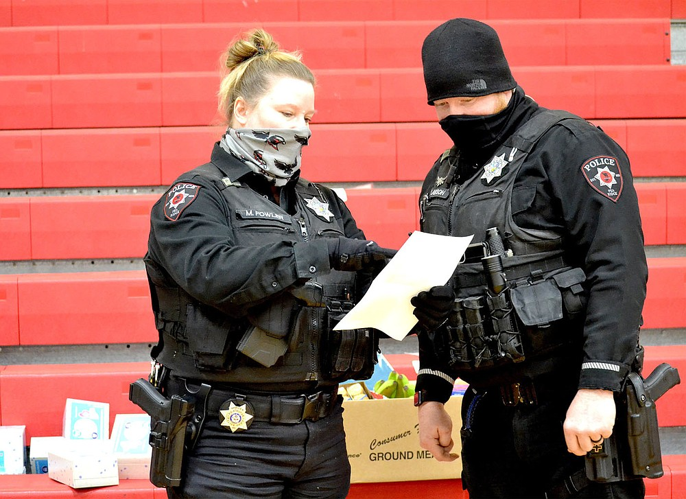 Pea Ridge Police officers Mindy Fowler and Justin Lawson check off a list of supplies for families during the natural gas outage in Pea Ridge Wednesday, Feb. 17, 2021. Supplies gathered for the warming station were delivered to families in need Wednesday by police officers.