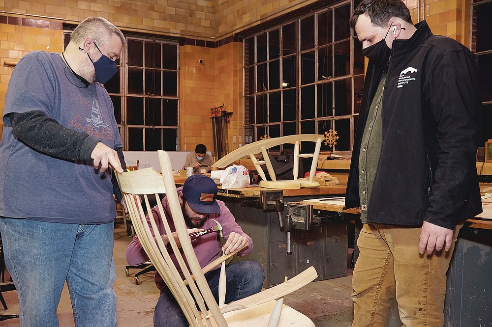 Jeff Rawlings, left, steadies a chair made by Caleb Peper, center, while Luke Barnett, director of the Sam Beauford Woodworking Institute, looks on at the shop on Jan. 189, 2021, in Adrian, Mich. Rawlings and Peper are students in the Furniture Making and Wood Design class at the institute. (Mike Dickie/The Daily Telegram via AP)