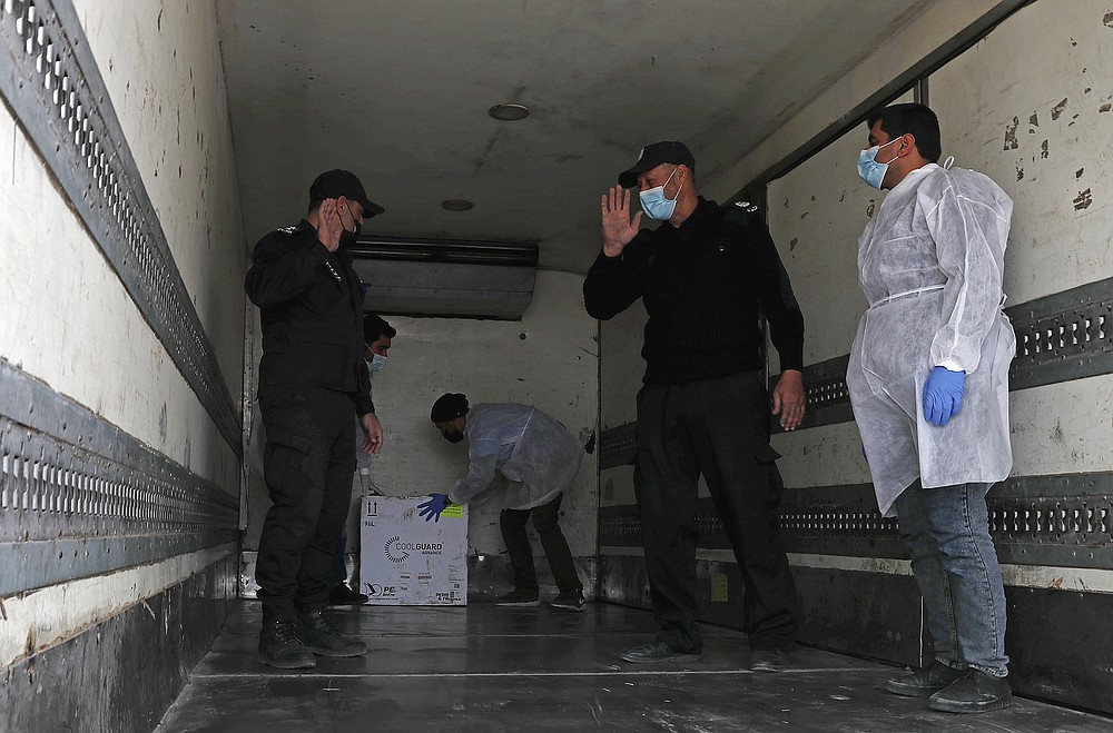 Medics and police officers guard a shipment of the Russian Sputnik V vaccine inside a truck at the Kerem Shalom border crossing, in Rafah, Gaza Strip, Wednesday, Feb. 17, 2021. The Palestinian Authority said Wednesday that it dispatched the first shipment of coronavirus vaccines to the Hamas-ruled Gaza Strip, two days after accusing Israel of preventing it from sending the doses amid objections from some Israeli lawmakers. (AP Photo/Adel Hana)
