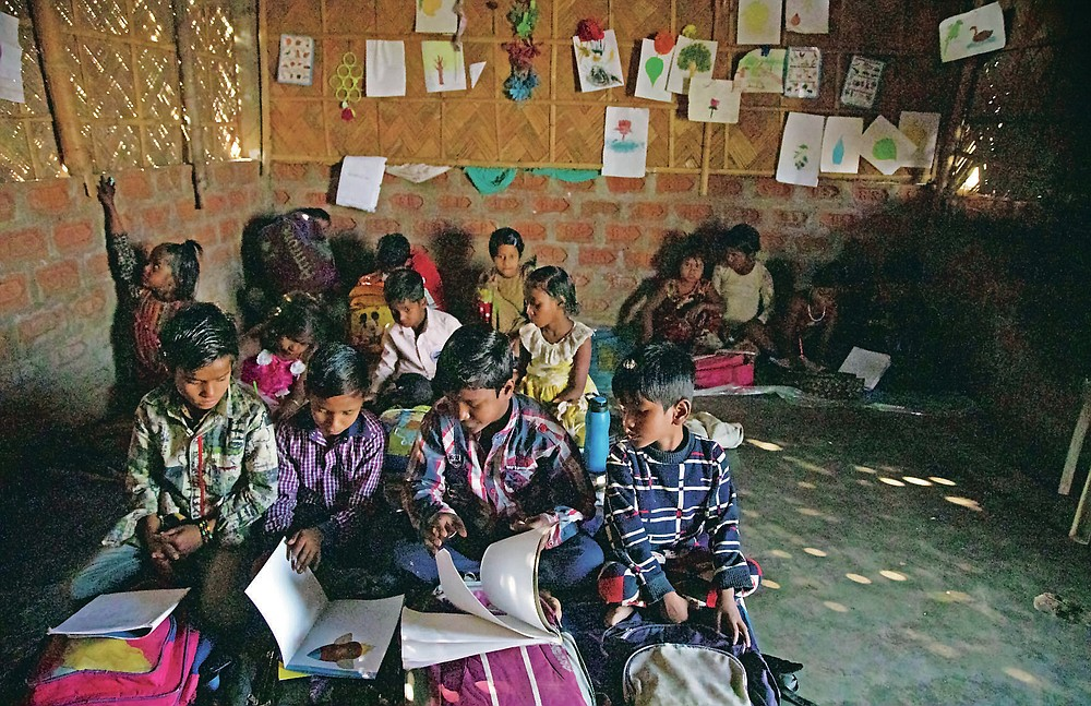 """Imradul Ali, 10, second from left, studies with other students at a school near a landfill on the outskirts of Gauhati, India, Friday, Feb. 5, 2021. Once school is done for the day, Ali, rushes home to change out of his uniform so that he can start his job as a scavenger in India's remote northeast. Coming from a family of scavengers or """"rag pickers,"""" Ali started doing it over a year ago to help his family make more money. Ali says he doesn't want to spend his life doing this, but he doesn't know what the future holds. (AP Photo/Anupam Nath)"""