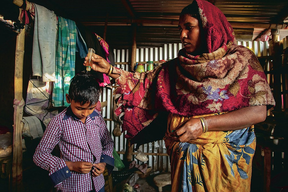 """Imradul Ali, 10, left, wears a shirt as his mother Anuwara Beghum, 30, pours oil on his head as he prepares to leave for school from his rented kitchen cum bedroom on the outskirts of Gauhati, India, Friday, Feb. 5, 2021. Once school is done for the day, Ali, rushes home to change out of his uniform so that he can start his job as a scavenger in India's remote northeast. Coming from a family of scavengers or """"rag pickers,"""" Ali started doing it over a year ago to help his family make more money. Ali says he doesn't want to spend his life doing this, but he doesn't know what the future holds. (AP Photo/Anupam Nath)"""