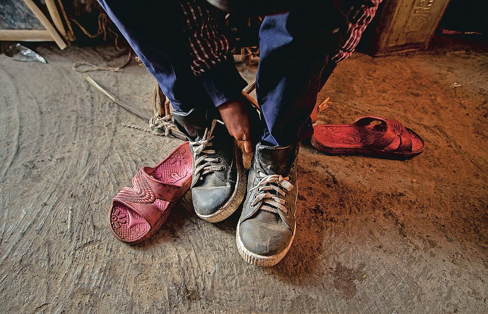 """Imradul Ali, 10, puts on a pair of shoes which he salvaged from a landfill before going to school from his rented kitchen cum bedroom on the outskirts of Gauhati, India, Friday, Feb. 5, 2021. Once school is done for the day, Ali, rushes home to change out of his uniform so that he can start his job as a scavenger in India's remote northeast. Coming from a family of scavengers or """"rag pickers,"""" Ali started doing it over a year ago to help his family make more money. Ali says he doesn't want to spend his life doing this, but he doesn't know what the future holds. (AP Photo/Anupam Nath)"""