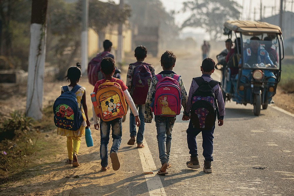 """Imradul Ali, 10, right, and his friends go to a school near a landfill on the outskirts of Gauhati, India, Friday, Feb. 5, 2021. Once school is done for the day, Ali, rushes home to change out of his uniform so that he can start his job as a scavenger in India's remote northeast. Coming from a family of scavengers or """"rag pickers,"""" Ali started doing it over a year ago to help his family make more money. Ali says he doesn't want to spend his life doing this, but he doesn't know what the future holds. (AP Photo/Anupam Nath)"""