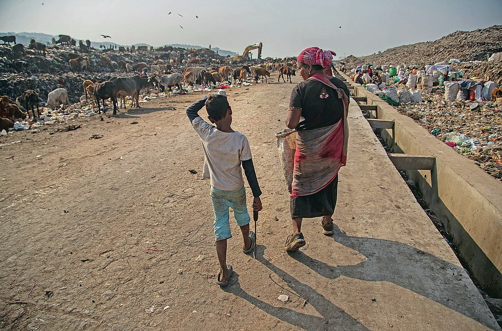 """Imradul Ali, 10, left, and his mother Anuwara Beghum, 30, arrive to look for recyclable material at a landfill on the outskirts of Gauhati, India, Thursday, Feb. 4, 2021. Once school is done for the day, Ali, rushes home to change out of his uniform so that he can start his job as a scavenger in India's remote northeast. Coming from a family of scavengers or """"rag pickers,"""" Ali started doing it over a year ago to help his family make more money. Ali says he doesn't want to spend his life doing this, but he doesn't know what the future holds. (AP Photo/Anupam Nath)"""
