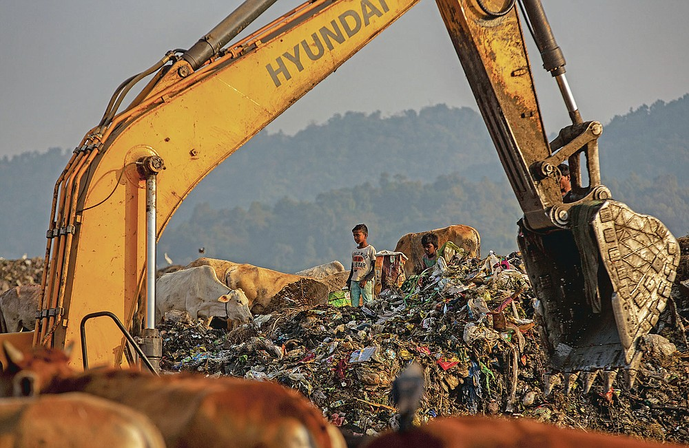 """Imradul Ali, 10, looks for recyclable material at a landfill on the outskirts of Gauhati, India, Thursday, Feb. 4, 2021. Once school is done for the day, Ali, rushes home to change out of his uniform so that he can start his job as a scavenger in India's remote northeast. Coming from a family of scavengers or """"rag pickers,"""" Ali started doing it over a year ago to help his family make more money. Ali says he doesn't want to spend his life doing this, but he doesn't know what the future holds. (AP Photo/Anupam Nath)"""
