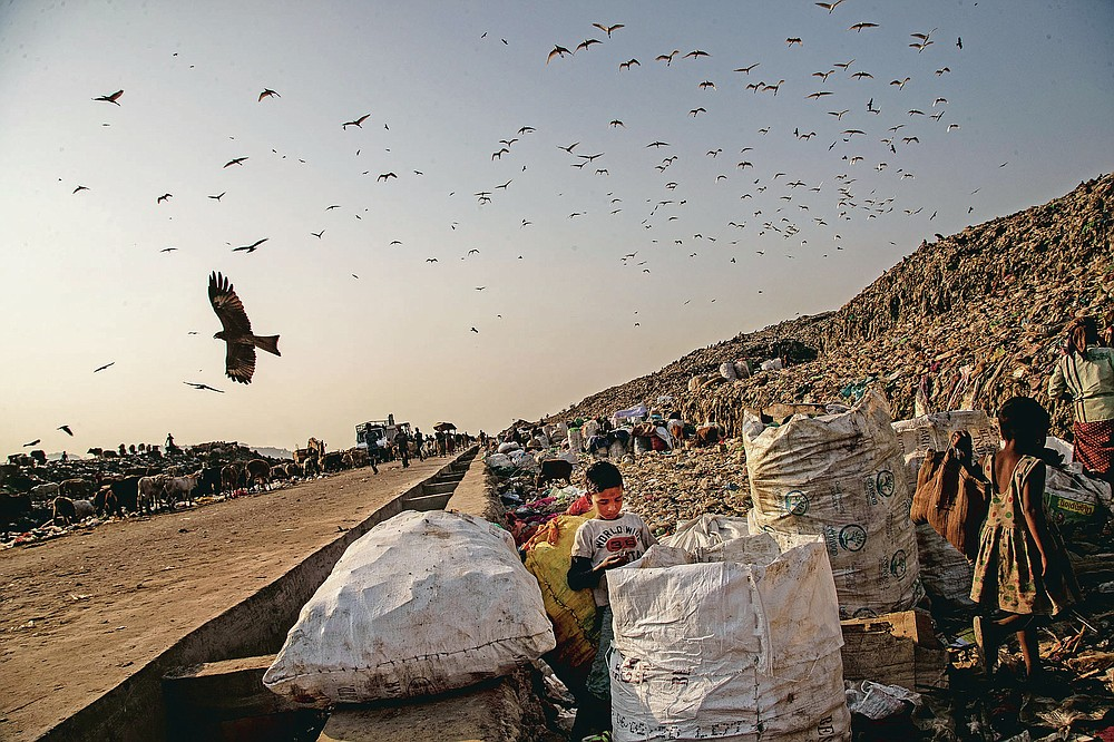 """Imradul Ali, 10, center, looks for recyclable material at a landfill on the outskirts of Gauhati, India, Thursday, Feb. 4, 2021. Once school is done for the day, Ali, rushes home to change out of his uniform so that he can start his job as a scavenger in India's remote northeast. Coming from a family of scavengers or """"rag pickers,"""" Ali started doing it over a year ago to help his family make more money. Ali says he doesn't want to spend his life doing this, but he doesn't know what the future holds. (AP Photo/Anupam Nath)"""