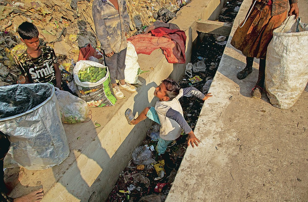 """Imradul Ali, 10, center, plays as he looks for recyclable material at a landfill on the outskirts of Gauhati, India, Thursday, Feb. 4, 2021. Once school is done for the day, Ali, rushes home to change out of his uniform so that he can start his job as a scavenger in India's remote northeast. Coming from a family of scavengers or """"rag pickers,"""" Ali started doing it over a year ago to help his family make more money. Ali says he doesn't want to spend his life doing this, but he doesn't know what the future holds. (AP Photo/Anupam Nath)"""
