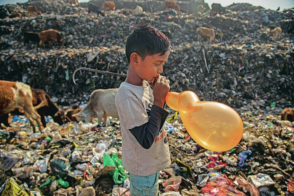 """Imradul Ali, 10, blows a balloon which salvaged from a landfill on the outskirts of Gauhati, India, Thursday, Feb. 4, 2021. Once school is done for the day, Ali, rushes home to change out of his uniform so that he can start his job as a scavenger in India's remote northeast. Coming from a family of scavengers or """"rag pickers,"""" Ali started doing it over a year ago to help his family make more money. Ali says he doesn't want to spend his life doing this, but he doesn't know what the future holds. (AP Photo/Anupam Nath)"""