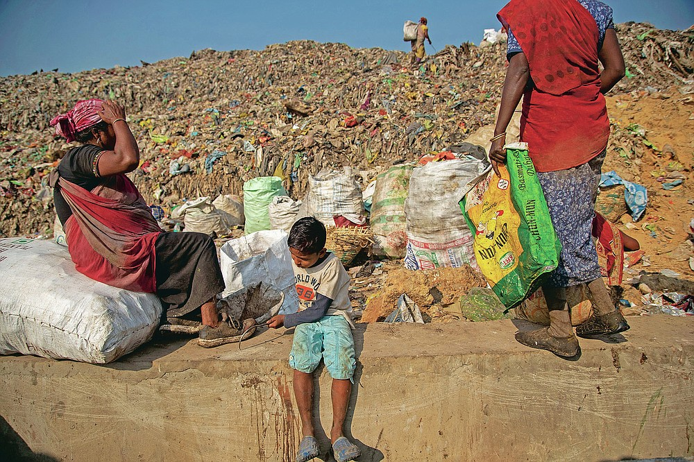 """Imradul Ali, 10, left, and his mother Anuwara Beghum, 30, take a break as they look for recyclable material at a landfill on the outskirts of Gauhati, India, Thursday, Feb. 4, 2021. Once school is done for the day, Ali, rushes home to change out of his uniform so that he can start his job as a scavenger in India's remote northeast. Coming from a family of scavengers or """"rag pickers,"""" Ali started doing it over a year ago to help his family make more money. Ali says he doesn't want to spend his life doing this, but he doesn't know what the future holds. (AP Photo/Anupam Nath)"""