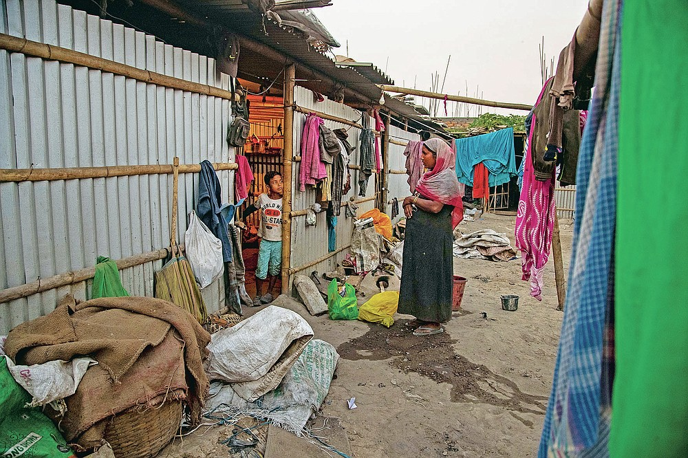 """Imradul Ali, 10, left, talks to his mother Anuwara Beghum, 30, at his rented house after returning from a landfill on the outskirts of Gauhati, India, Thursday, Feb. 4, 2021. Once school is done for the day, Ali, rushes home to change out of his uniform so that he can start his job as a scavenger in India's remote northeast. Coming from a family of scavengers or """"rag pickers,"""" Ali started doing it over a year ago to help his family make more money. Ali says he doesn't want to spend his life doing this, but he doesn't know what the future holds. (AP Photo/Anupam Nath)"""