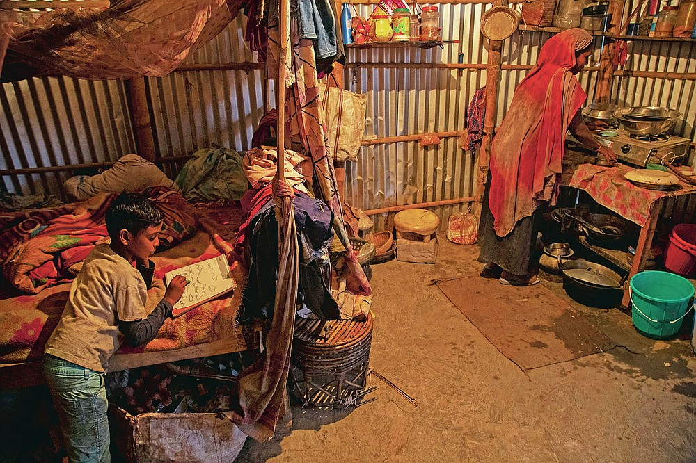"""Imradul Ali, 10, left, draws on his copy book as his mother Anuwara Beghum, 30, prepares food in their rented kitchen cum bedroom house near a landfill on the outskirts of Gauhati, India, Thursday, Feb. 4, 2021. Once school is done for the day, Ali, rushes home to change out of his uniform so that he can start his job as a scavenger in India's remote northeast. Coming from a family of scavengers or """"rag pickers,"""" Ali started doing it over a year ago to help his family make more money. Ali says he doesn't want to spend his life doing this, but he doesn't know what the future holds. (AP Photo/Anupam Nath)"""