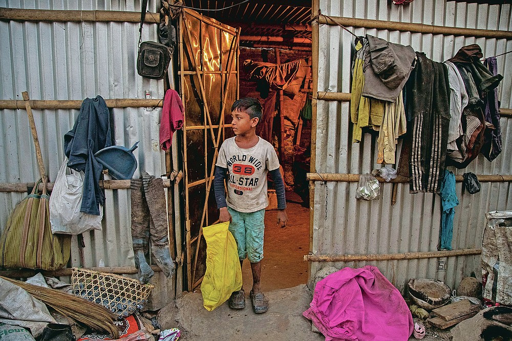 """Imradul Ali, 10, places in front of his one bedroom rented house, a yellow bag which contains recyclable material he collected from a landfill on the outskirts of Gauhati, India, Thursday, Feb. 4, 2021. Once school is done for the day, Ali, rushes home to change out of his uniform so that he can start his job as a scavenger in India's remote northeast. Coming from a family of scavengers or """"rag pickers,"""" Ali started doing it over a year ago to help his family make more money. Ali says he doesn't want to spend his life doing this, but he doesn't know what the future holds. (AP Photo/Anupam Nath)"""