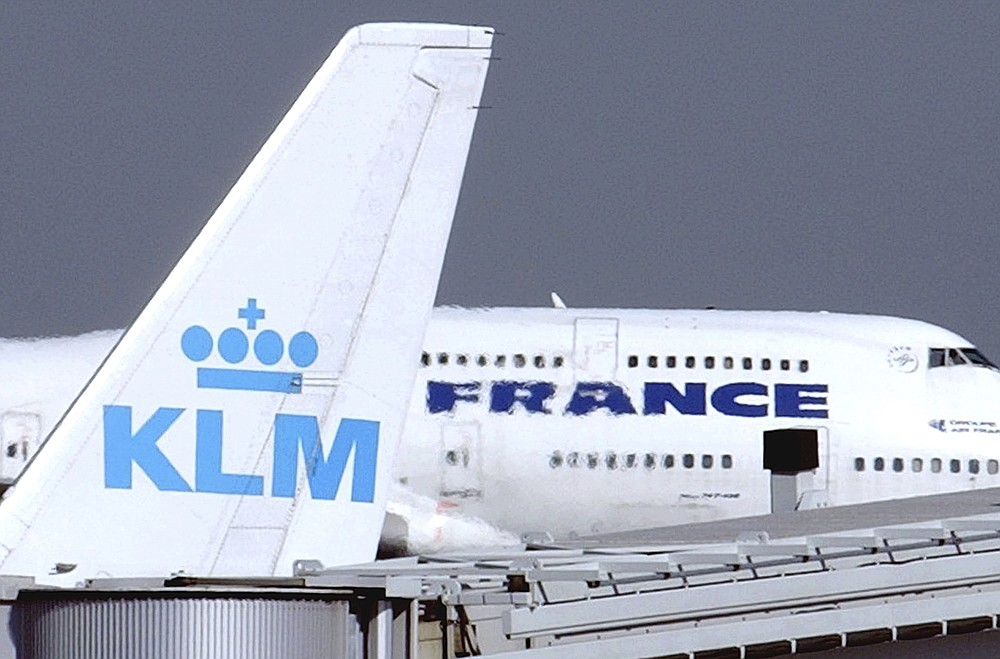 FILE - In this Sept. 30, 2003 file photo, an Air France jumbo jet rolls behind the tail of a KLM Royal Dutch airliner at Charles de Gaulle airport in Roissy, north of Paris. Air France-KLM plunged to a 7.1 billion euro ($8.5 billion) loss in 2020 as the global pandemic grounded planes and halted travel plans worldwide causing a 67% slump in passenger numbers at the French-Dutch aviation giant. (AP Photo/Remy de la Mauviniere, File)