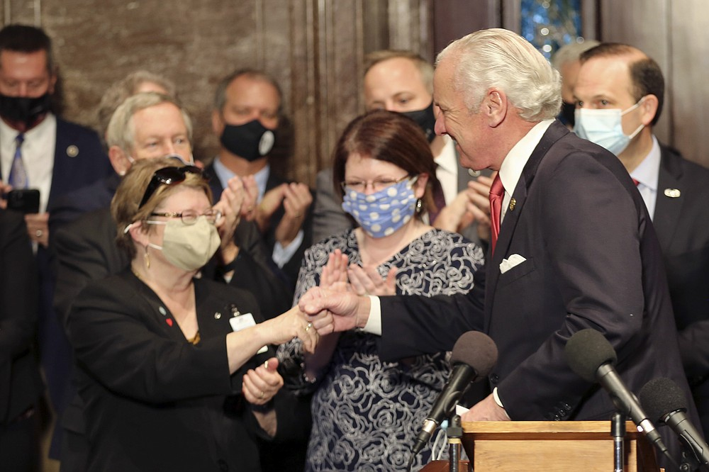 "South Carolina Gov. Henry McMaster, right, fist bumps South Carolina Citizens for Life Executive Director Holly Gatling, left, before McMaster signed a bill banning almost all abortions in the state on Thursday, Feb. 18, 2021, in Columbia, S.C. On the same day, Planned Parenthood filed a federal lawsuit to stop the measure from going into effect. The state House approved the ""South Carolina Fetal Heartbeat and Protection from Abortion Act"" on a 79-35 vote Wednesday and gave it a final procedural vote Thursday before sending it to McMaster.  (AP Photo/Jeffrey Collins)"