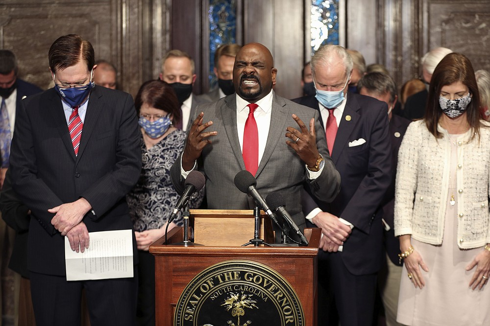 Greenwood pastor Tony Foster prays during a ceremony where South Carolina Gov. Henry McMaster signed a bill banning almost all abortions in the state on Thursday, Feb. 18, 2021, in Columbia, S.C.  On the same day, Planned Parenthood filed a federal lawsuit to stop the measure from going into effect.  (AP Photo/Jeffrey Collins)