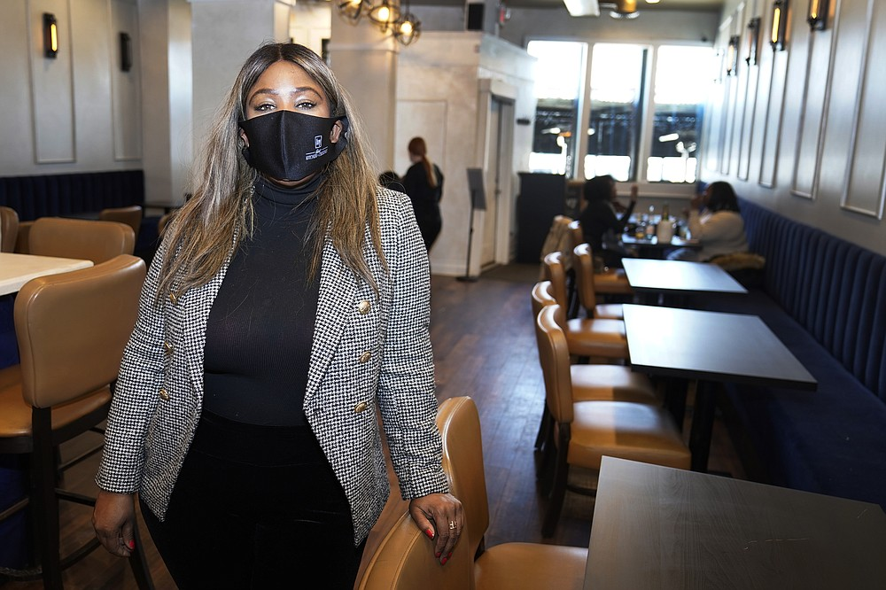 Nya Marshall, owner of Ivy Kitchen & Cocktails is seen in her restaurant, Saturday, Feb. 6, 2021 in Detroit. Marshall is worried about President Biden's plan to raise the minimum wage to $15 which could put her and other restaurants out of business in the middle of the pandemic. (AP Photo/Carlos Osorio)