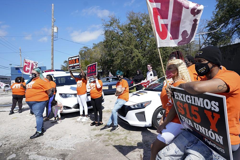 Cristian Cardona, sitting on a car hood, center, an employee at a McDonald's, attends a rally for a $15 an hour minimum wage Tuesday, Feb. 16, 2021, in Orlando, Fla. (AP Photo/John Raoux)