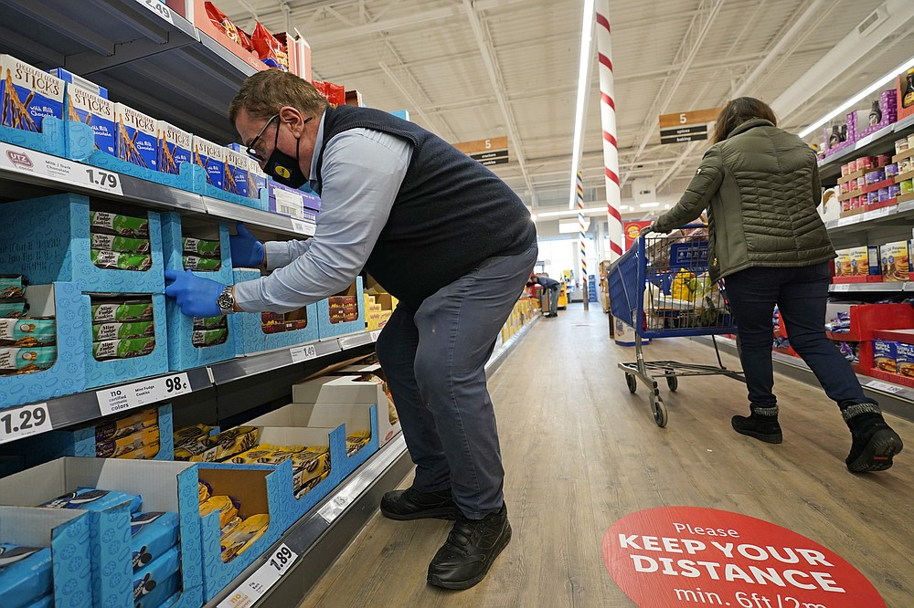 """In this Thursday, Feb. 4, 2021 photo, grocery supervisor Joseph Lupo, left, arranges cookies in the shelves at the Lidl food market in Lake Grove, N.Y., where he works after getting the first dose of the COVID-19 vaccination earlier in the day. Lupo, who fell ill with the virus in March, was elated to get his first vaccine dose. """"I never ever want to get COVID again, or see anybody else get it,"""" said Lupo, 59. (AP Photo/Kathy Willens)"""