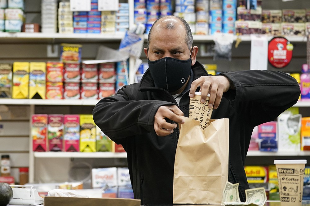 Bodega owner Francisco Marte prepares coffee for a customer, Wednesday, Feb. 10, 2021, at his store in the Bronx borough of New York. Marte, president of the Bodega and Small Business Association of New York, said he has been lobbying local officials to set aside appointments for bodega workers, many of whom are unaware they are eligible. He hopes that the recent opening of a large vaccination site at Yankee stadium will make access easier. (AP Photo/Kathy Willens)