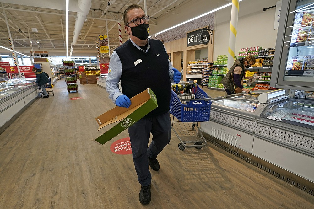 In this Thursday, Feb. 4, 2021 photo, Lidl employee Joseph Lupo makes his rounds tidying up in the Long Island grocery store where he works in Lake Grove, N.Y. Earlier in the day, Lupo received the first dose of the COVID-19 vaccination at a Suffolk County Community College vaccination hub located in a giant arena repurposed for vaccinations. (AP Photo/Kathy Willens)